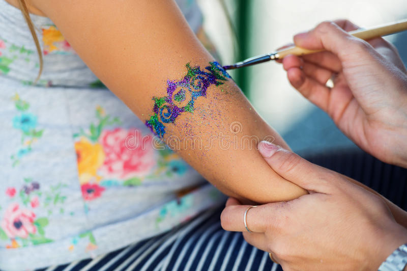 Little girl getting glitter tattoo royalty free stock photos