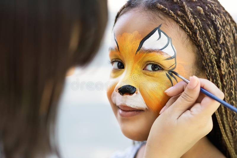Little girl getting her face painted by face painting artist. stock images