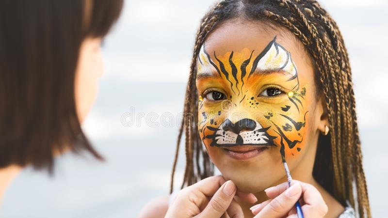 Little girl getting her face painted by face painting artist. Kids facial art. Little girl getting her face painted by face painting artist like tiger, free royalty free stock images