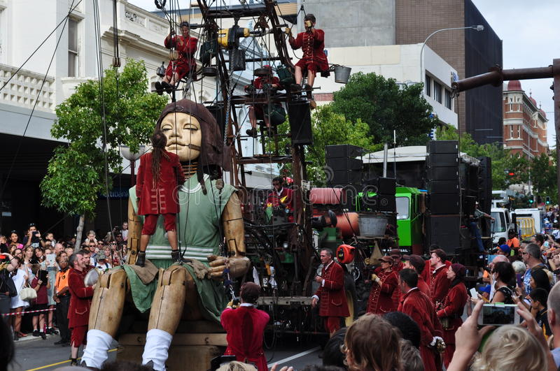 The little girl giant in Perth streets Western Australia with Lillputians. Teamwork on the girl giant puppet by lillputians in Perth streets Western Australia royalty free stock photo