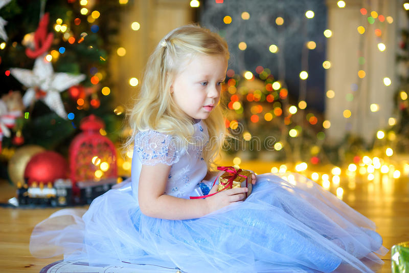 Little girl with a gift. Beautiful little girl, sits on a floor with a gift in hands, in a festive interior. A set of bright sparks on a background royalty free stock photos