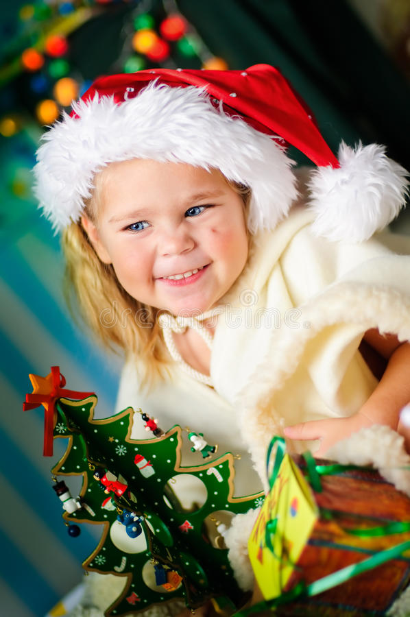 Little girl with gift and Christmas tree stock photo