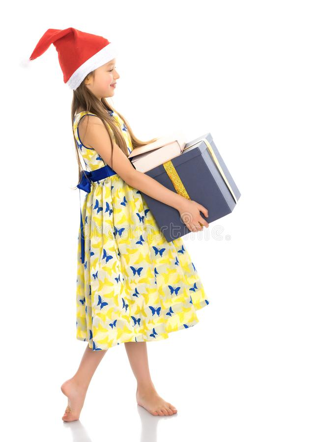 A little girl with a gift in a Santa Claus hat. royalty free stock image