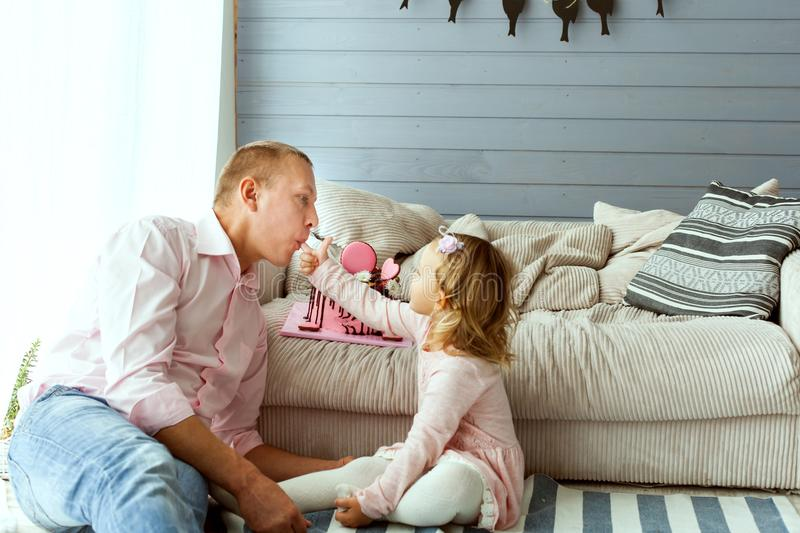 Little girl with her dad eating cake. royalty free stock images