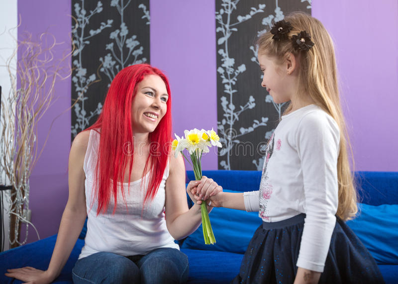 Little girl giving flowers to her mom-happy family stock images