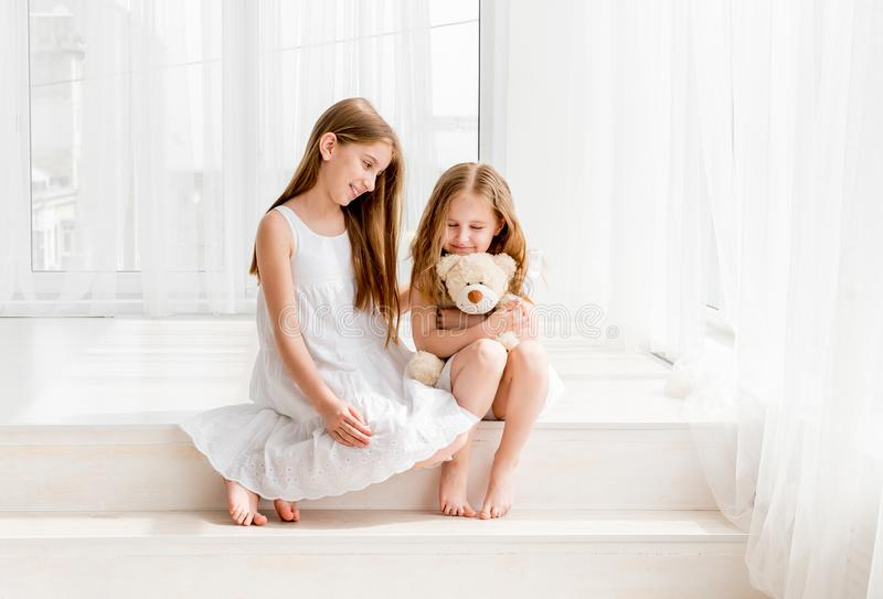 Little girl giving her teddy bear toy to older sister stock photo
