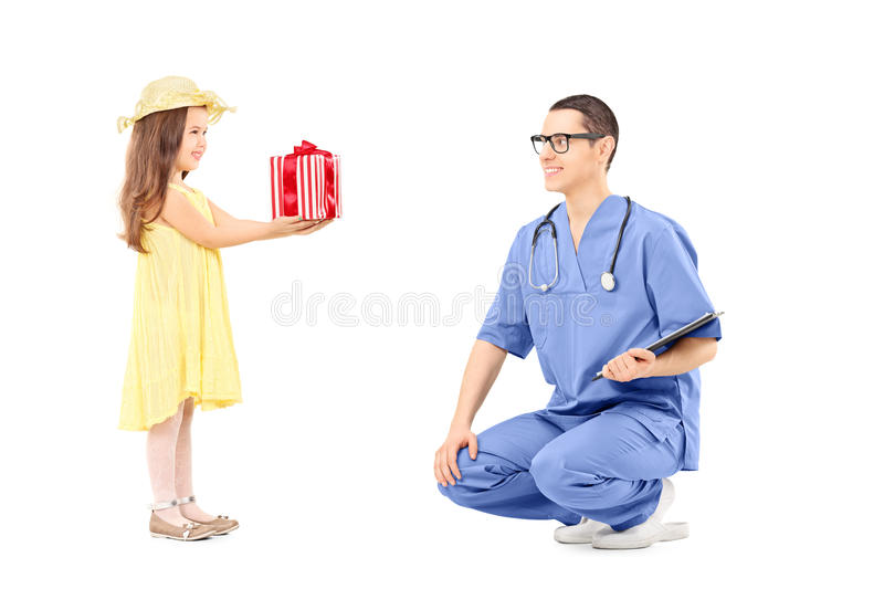 Little girl giving a present to male doctor royalty free stock photo