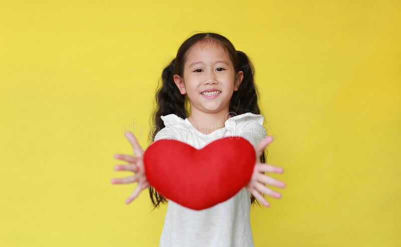 Little girl giving red heart for Valentine`s Day for you on yellow background. Focus at kid face stock photo