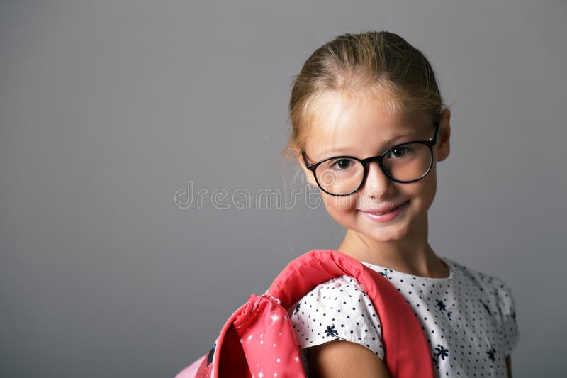 Little girl with glasses and backpack. Ready for school royalty free stock images
