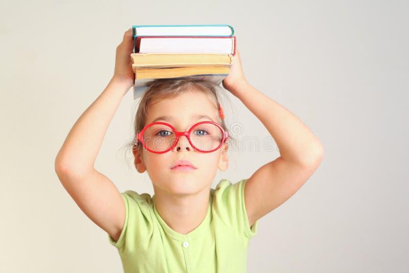 Little girl in glasses hold books