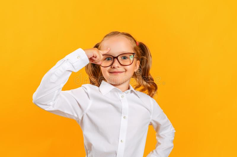 A little girl with glasses holds a finger to her head, an idea came up in a child. royalty free stock photos