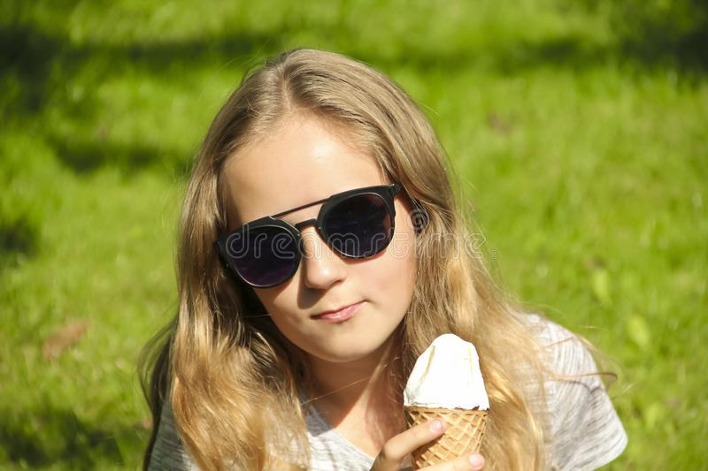 Little girl with glasses with ice cream on nature grass stock images