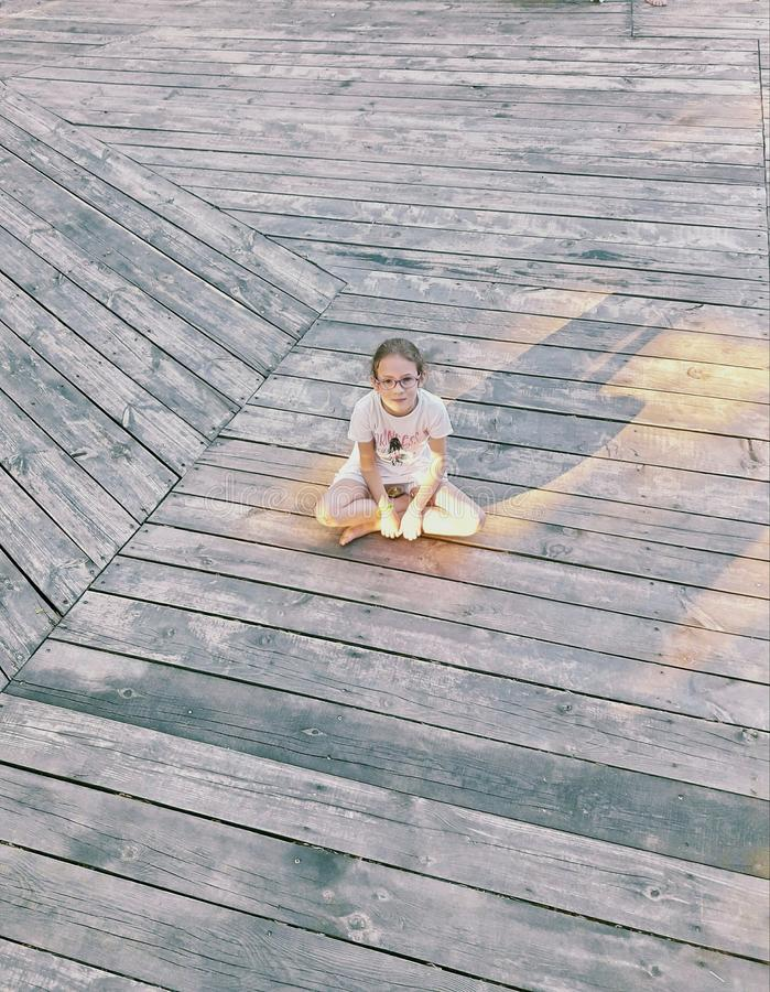 A little girl is sitting in a lotus pose on a wooden floor stock image