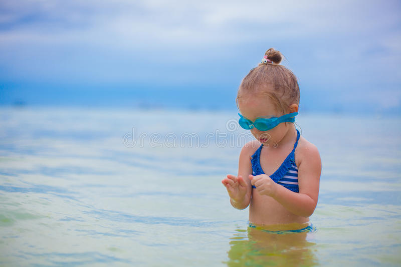 Little girl with glasses for swimming swims and. Dives in the sea. This image has attached release royalty free stock image