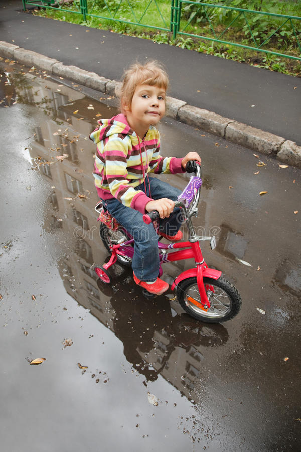 Download Little Girl Goes On A Bicycle On Wet Asphalt Royalty Free Stock Image - Image: 13803226