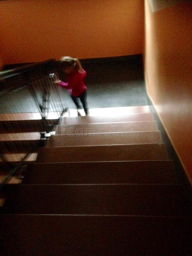 Little girl going downstairs royalty free stock image