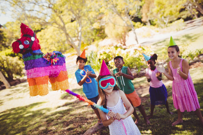 Little girl is going to broke the pinata for their birthday. In a park royalty free stock photography