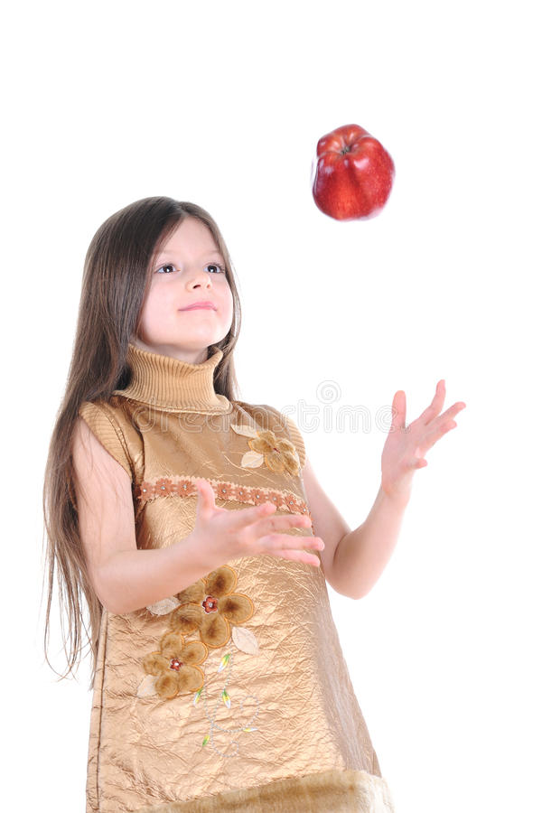 Download Little Girl In A Gold Dress Catches A Big Red Apple Royalty Free Stock Images - Image: 14184409