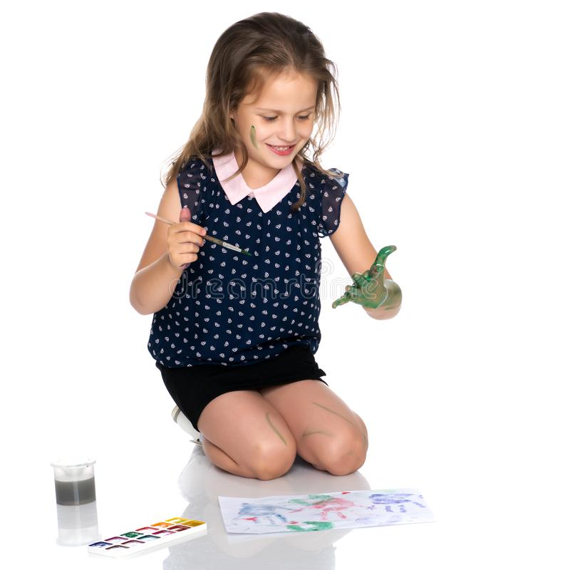 The little girl got dirty with the paints. stock photo