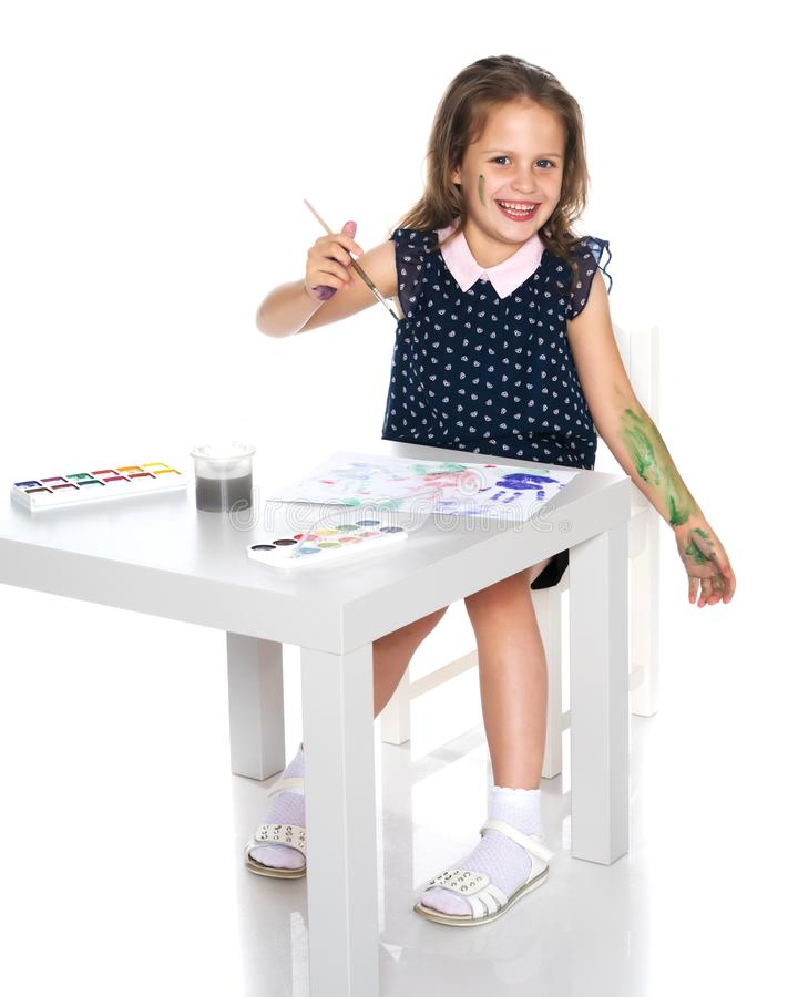 The little girl got dirty with the paints. royalty free stock photo