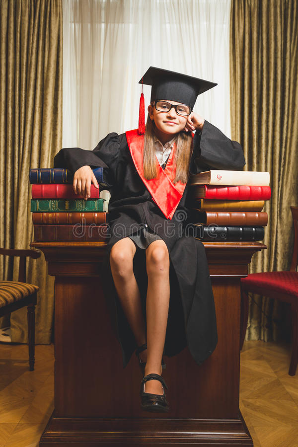 Little girl in graduation cap posing on table at library. Toned photo of little girl in graduation cap posing on table at library stock photos