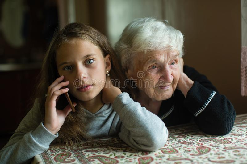Little girl granddaughter talking on a mobile phone and grandmother her listens. Family. Little girl granddaughter talking on a mobile phone and grandmother her royalty free stock photography