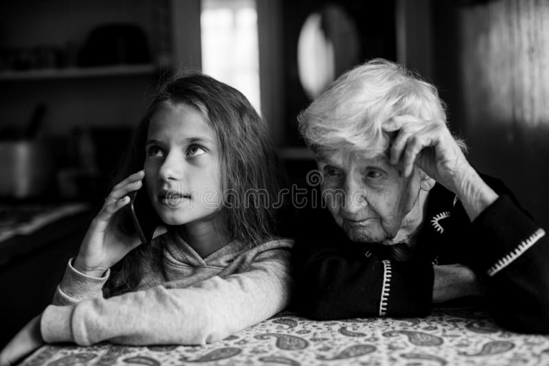 Little girl granddaughter talking on a mobile phone and grandmother her listens. Black and white photo stock photos