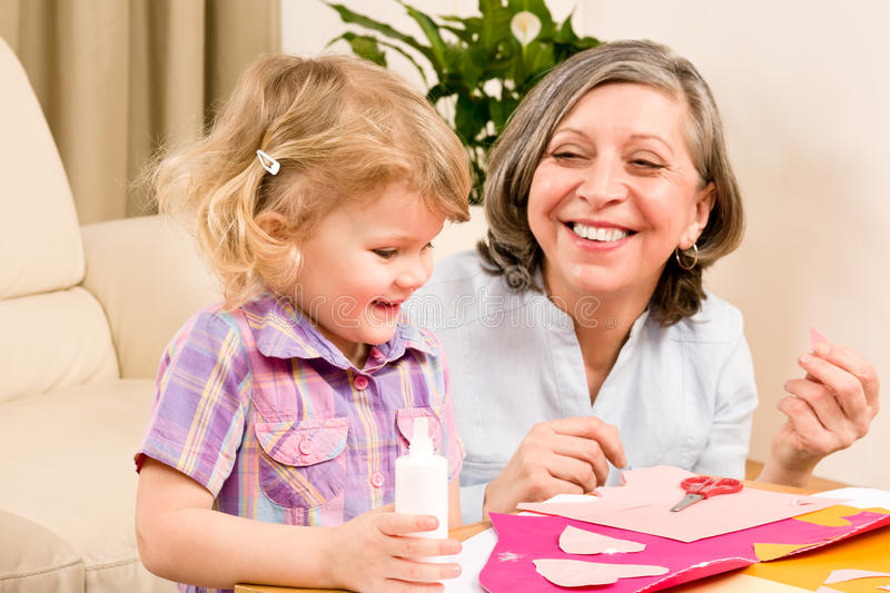 Little Girl With Grandmother Play Glue Paper Royalty Free Stock Image