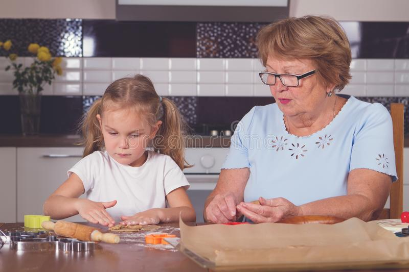 Little girl and grandmother roll out the dough stock image
