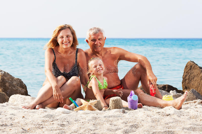 Little girl with grandparents on the beach royalty free stock photo