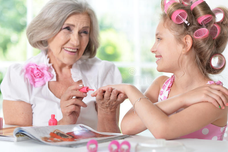 Little Girl With Granny With Magazine And Nail Polish Stock Image ...