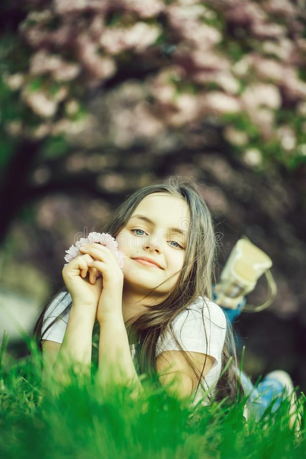 Little girl on grass in bloom stock photo