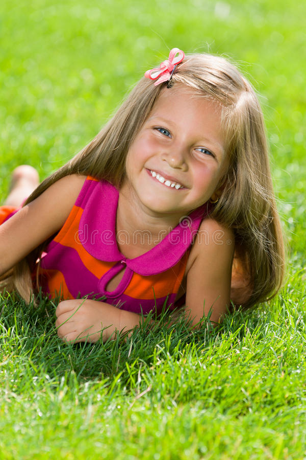 Little girl is on the grass stock photography