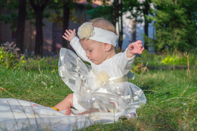 A little girl on the grass. Little girl, grass, white dress, baby, playing on the grass, child in nature, the baby lies stock images
