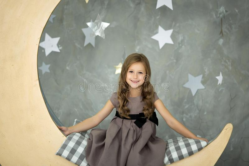 Little girl in gray dress is sitting on big moon stock photography