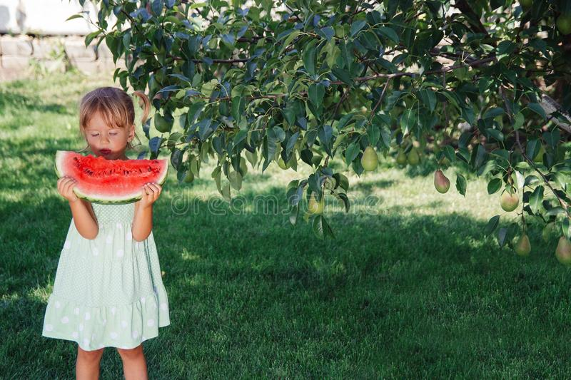 Little girl in green dress, barefoot standing in the park with big slice watermelon. stock photos