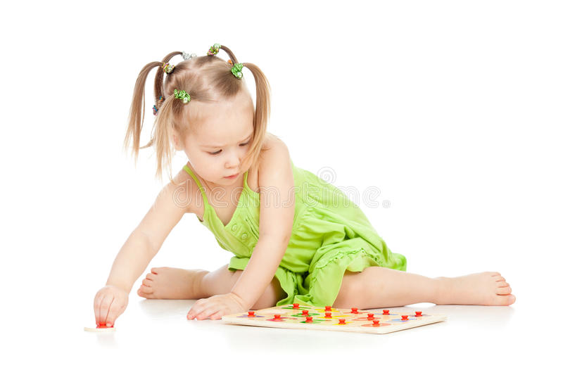 Little girl in green dress playing puzzle game royalty free stock images