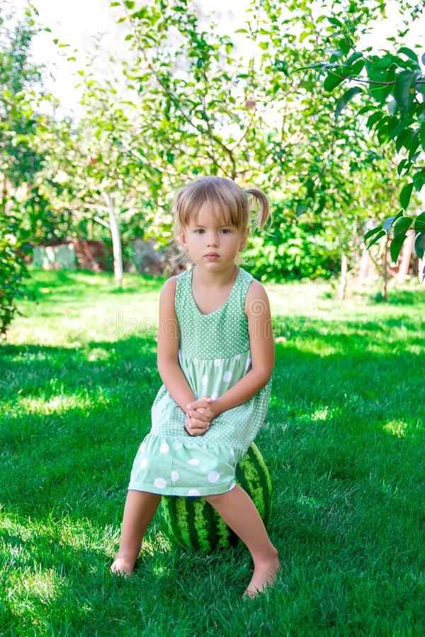 Little girl in green dress sitting on the watermelon in the park, outdoor. Summer. Sad child. Little girl in green dress sitting on the watermelon in the park royalty free stock photography