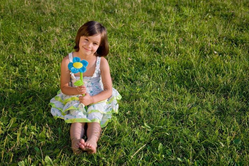 Little girl on green grass royalty free stock images
