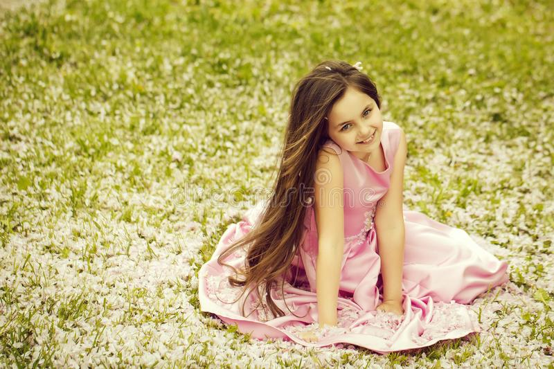 Little girl on green grass with petals royalty free stock image