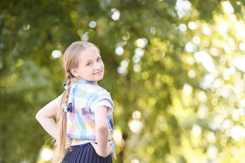 Little girl in green sunny forest along. Fun schoolgirl outside. Selective focus royalty free stock photography