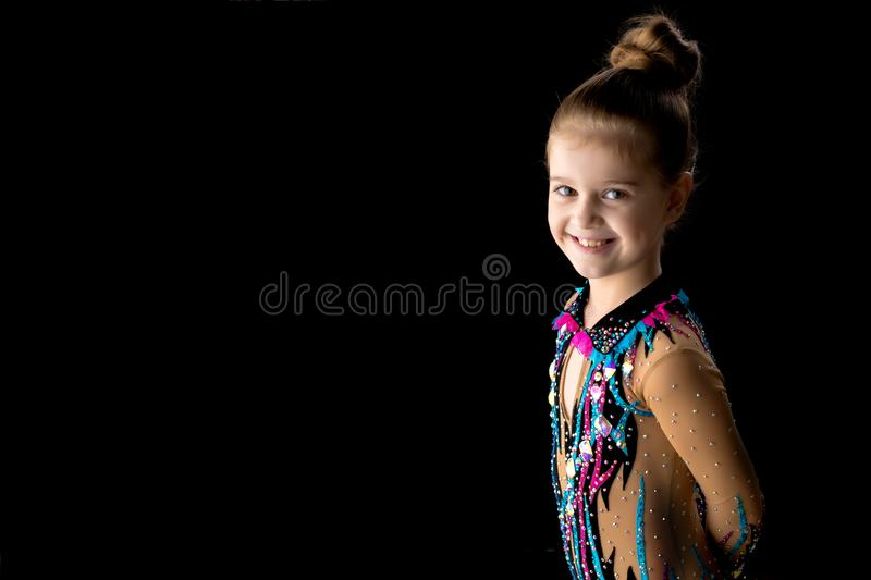 Little girl gymnast in a beautiful sporty swimsuit on a black ba royalty free stock photo