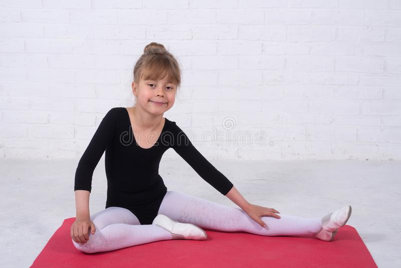 A little girl in a gymnastic swimsuit performing exercises, free space royalty free stock photos