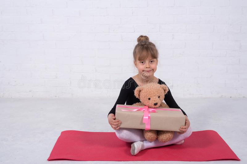 Little girl in the gymnastic swimsuit and with a teddy bear, free space stock photography