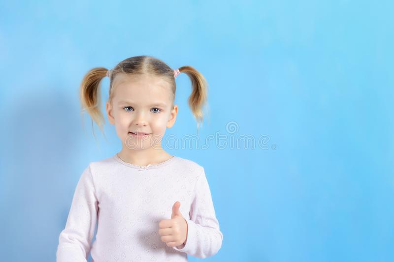 A little girl with a hair two tails. Cute baby with blond hair showing sign super. stock image