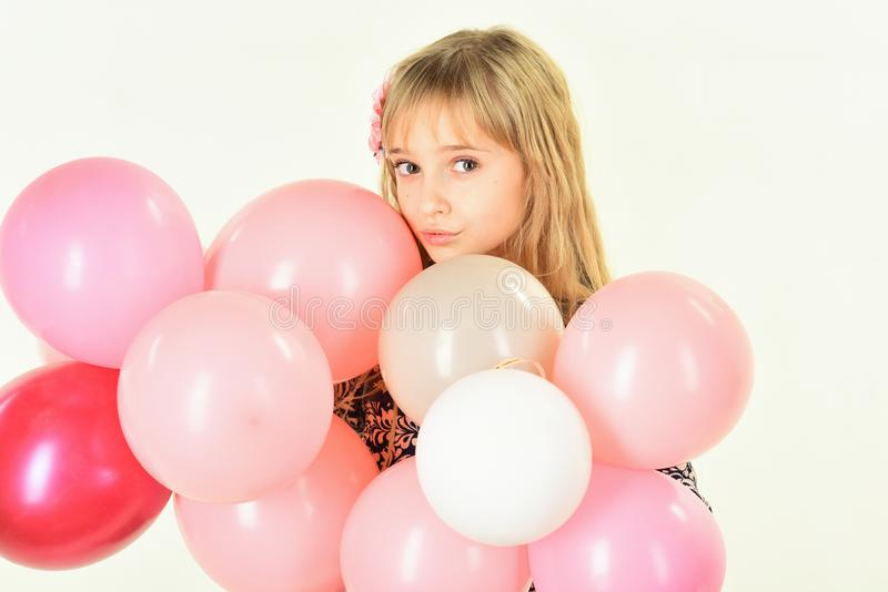 Little girl with hairstyle hold balloons. Beauty and fashion, punchy pastels. Kid with balloons at birthday. Small girl stock photography