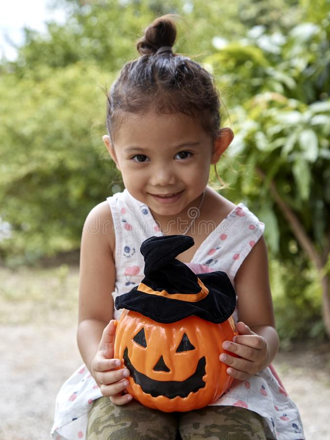 Little girl with halloween pumpkin royalty free stock photo