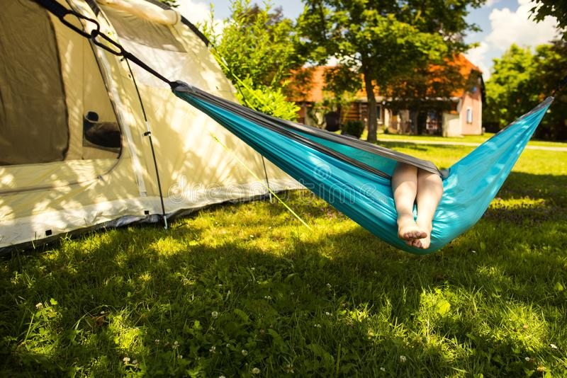 Little girl in the hammock and the tent in background stock images