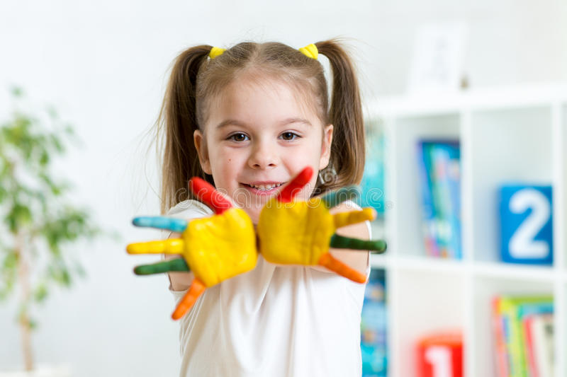 Little girl with hands in paint on nursery stock images