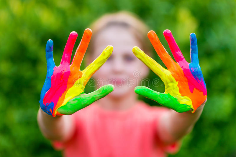 Little girl with hands painted in colorful paints ready for hand prints royalty free stock images